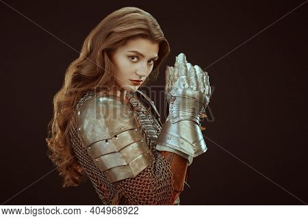 Beautiful medieval woman warrior in chain mail and plate armor on a black background.