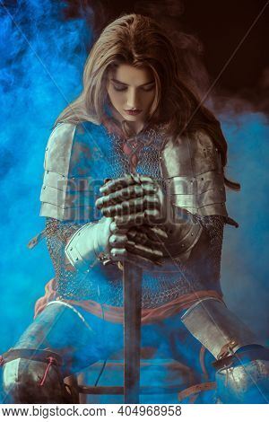A beautiful noble warrior woman in chain mail and plate armor sits, leaning on her sword and bowing her head. Medieval knight.