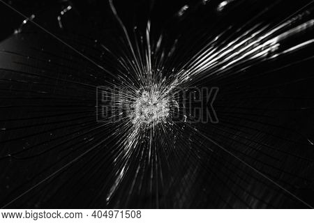Broken Glass Background With Bullet Hole Over Black Background. Shattered And Broken Glass Pieces Wi