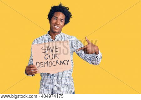 Handsome african american man with afro hair holding save our democracy protest banner smiling happy pointing with hand and finger