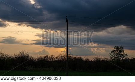 Silhouettes Of Garden Trees And Power Line In Cloudy Weather In The Evening At Sunset. Spring Season