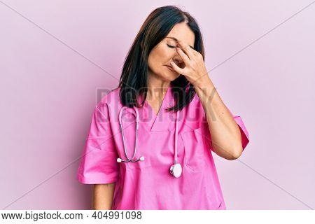 Middle age brunette woman wearing doctor uniform and stethoscope tired rubbing nose and eyes feeling fatigue and headache. stress and frustration concept.