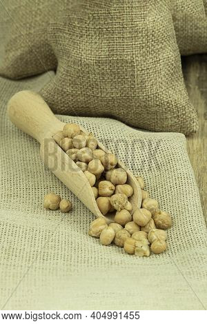 Chickpea Grains In A Bag On A Wooden Background With Space For Text. Chickpea Seeds On A Wooden Spoo