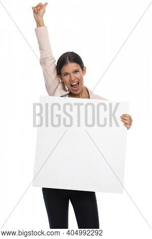 enthusiastic young woman with empty board holding arm in the air, screaming and having fun on white background in studio