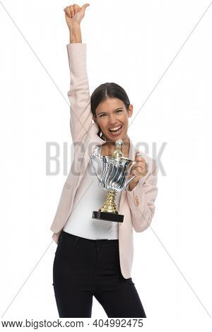 enthusiastic smart casual girl in pink jacket holding hands up, holding trophy and celebrating victory on white background in studio