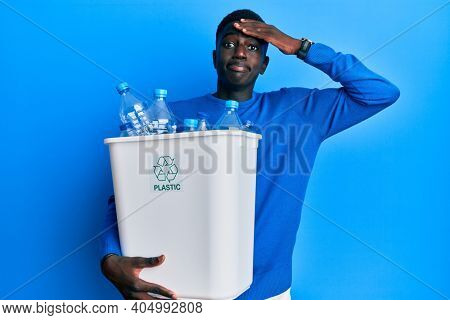 Young african american man holding recycling wastebasket with plastic bottles stressed and frustrated with hand on head, surprised and angry face