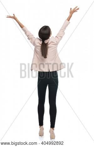 enthusiastic businesswoman in pink jacket holding hands in the air and celebrating, cheering victory and standing isolated on white background in studio