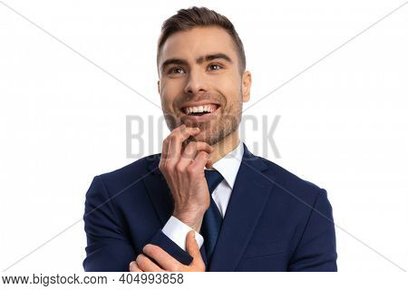portrait of fascinated bearded man in elegant navy blue suit holding hand to chin, looking up and showing admiration, smiling and posing on white background in studio