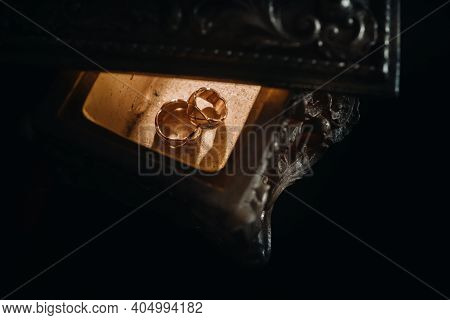 Gold Wedding Rings Lie On An Antique Jewelry Box. Wedding Rings For Ceremonies