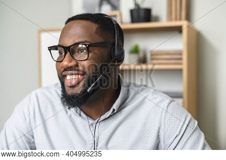 Young And Handsome African-american Employee Wearing Glasses, Headphones With A Microphone, Talking