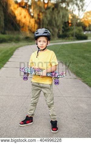 Happy Caucasian Boy In Grey Helmet Standing With Skateboard On Road In Park On Summer Day. Seasonal