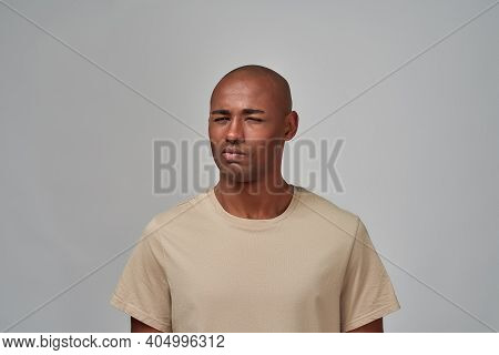 Man Pursing His Lips And Squinting Eyes While Staring With Mistrust At A Person Outside The Frame