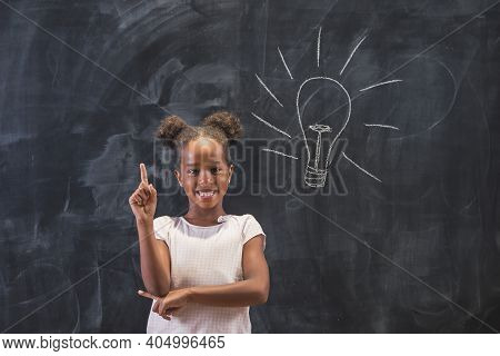 Elementary School Girl Standing In Front Of A Chalkboard In Classroom, Happy After Coming Up With An