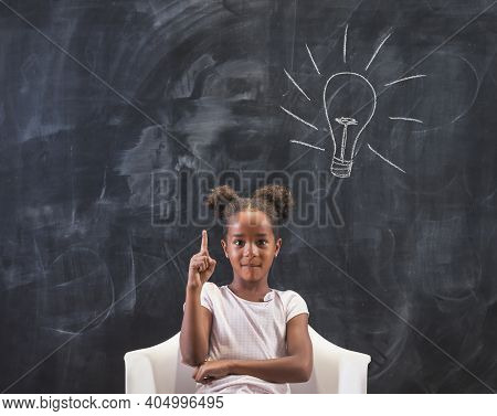 Elementary School Girl Sitting In Chair In Front Of A Chalkboard In Classroom, Happy After Coming Up