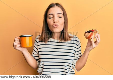 Young beautiful woman drinking coffee and eating pastry looking at the camera blowing a kiss being lovely and sexy. love expression.