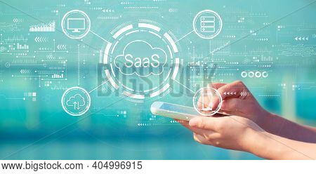 Saas - Software As A Service Concept With Person Holding A White Smartphone
