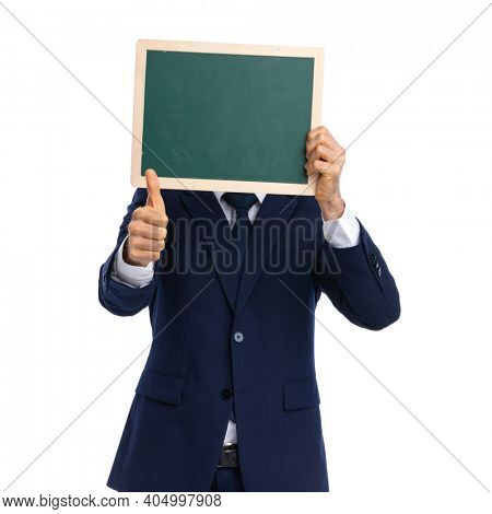 shy young man in elegant navy blue suit on white background hiding behind blackboard and making thumbs up sign in studio