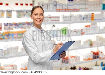 medicine, profession and healthcare concept - happy smiling female doctor or pharmacist in white coat with clipboard and pen writing medical report over pharmacy background