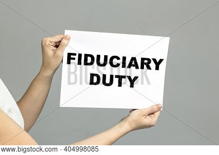 Fiduciary Duty Text Is Written On Paper. Business Woman Holding A Sheet With Fiduciary Duty An Inscr