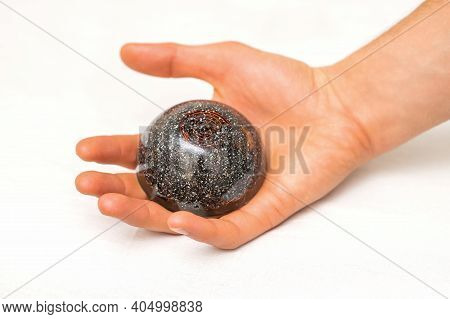 Closeup Of Massage Stone Lying In The Hand Of Male Massage Therapist On A White Background