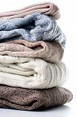 A stack of warm winter knitted sweaters on a white background isolated. poster