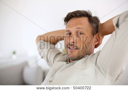 Man relaxing with outstretched arms behind head