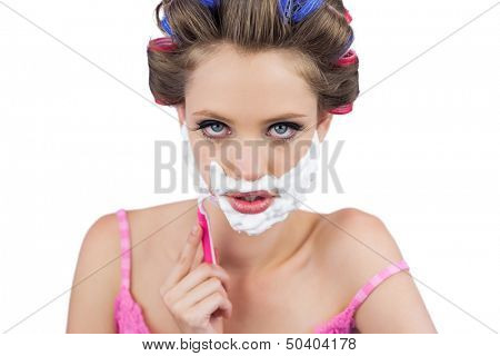 Serious model in hair curlers shaving her face on white background
