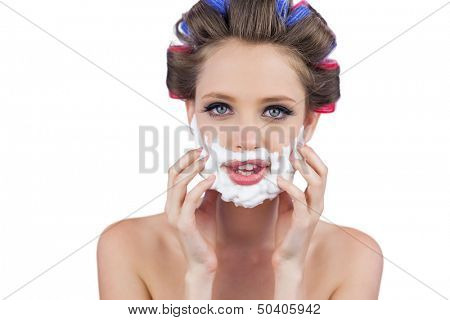 Model touching her face with shaving foam on white background