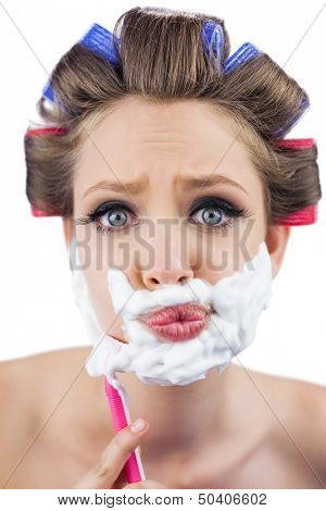 Curious model in hair curlers posing with shaving foam and razor on white background