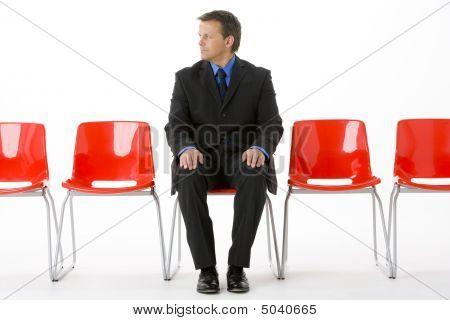 Empresario sentado en la fila de sillas vacías
