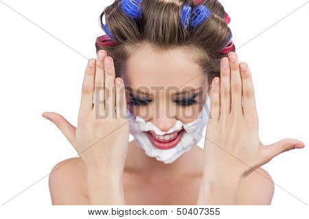 Pensive woman with hands up and shaving foam on face on white background