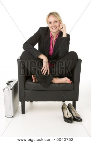 Businesswoman Sitting In Leather Chair With Her Shoes Off