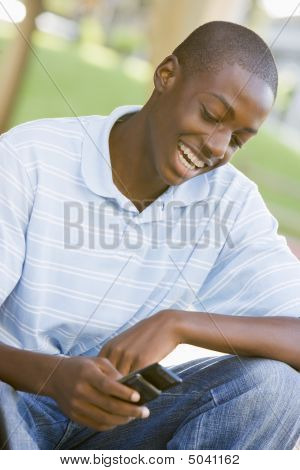 Teenage Boy Sitting Outdoors Using Mobile Phone