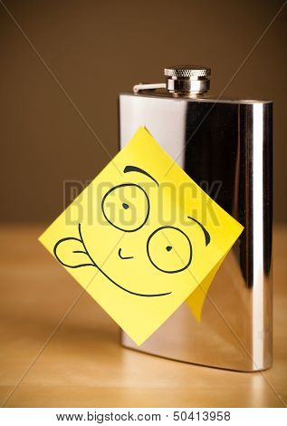 Drawn smiley face on a post-it note sticked on a hip flask poster