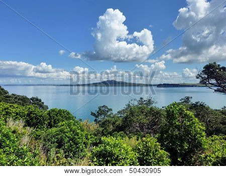 View Over Onto The Sea With Island And White Clouds In The Background