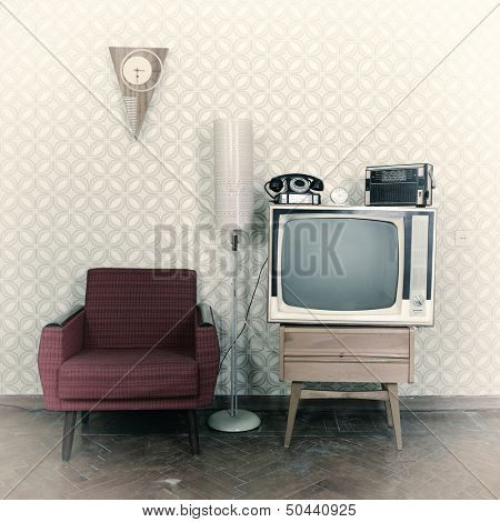 Vintage room with wallpaper, old fashioned armchair, retro tv, phone, clocks, radio player and standart lamp. Image toned, noise added and vignetted