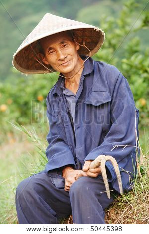 asian chinese farm man worker with shovel in china agriculture field