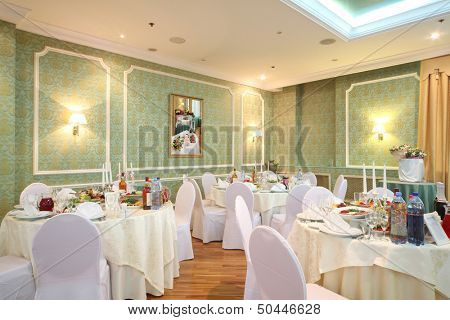 Elegantl hall with tables in a restaurant decorated for a wedding celebration, my photo in frame on wall