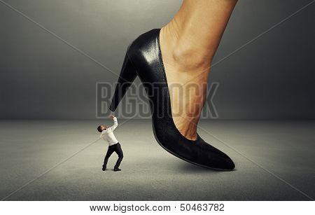concept photo of man under big female heel