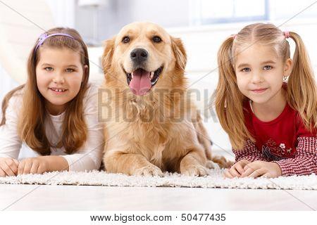 Little girls lying prone on floor, golden retriever between them.