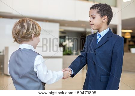 Caucasian boy and mulatto boy in business clothes shake hands in a business center