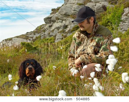 a hunter and his dog (gordon setter) in cotton grass poster