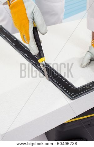 Worker Cutting An Insulation Panel With A Scale Model Knife