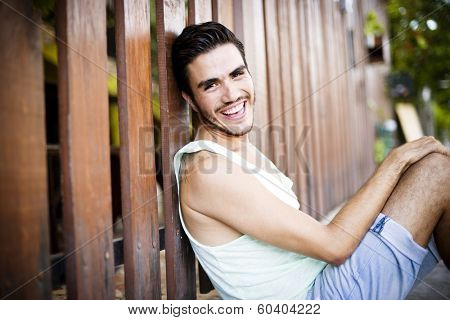 Portrait of a young handsome man,sitting outdoors, with toupee in urban background