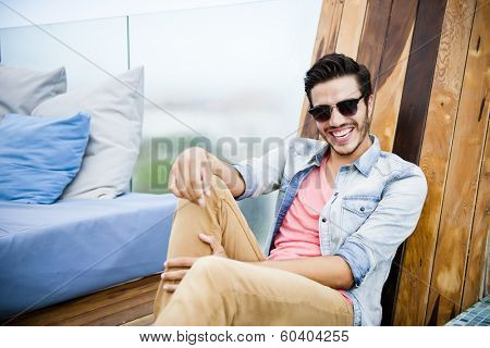 Portrait of a young handsome man,sitting outdoors, with toupee and sunglasses in urban background