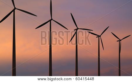Wind Turbines Against Red Sky