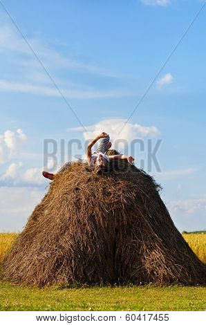 Little Cheerful Girl On Hayrick In Wheat Field.