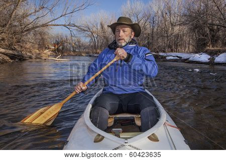 senior canoe paddler in a decked expedition canoe on the Cache la Poudre River, Fort Collins, Colorado, winter or early spring