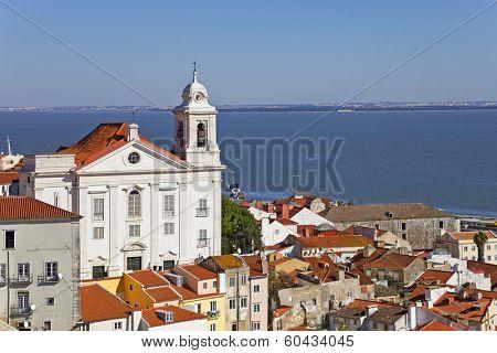 Alfama District with Santo Estevao Church and the Tagus River estuary seen from Miradouro de Santa Luzia. Lisbon, Portugal.