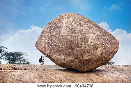Man Pushing A Big Stone